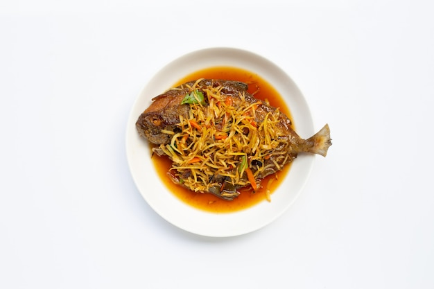 Gefrituurde vis met gember en sojasaus op witte schotel plaat.