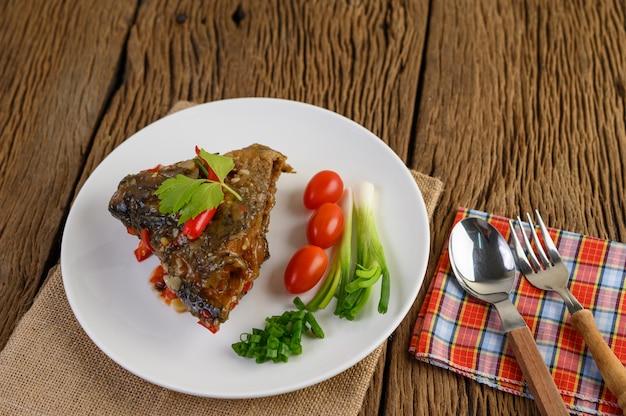 Gefrituurde viskoppen gegarneerd met pepers op een witte plaat met tomaten en lente-uitjes.