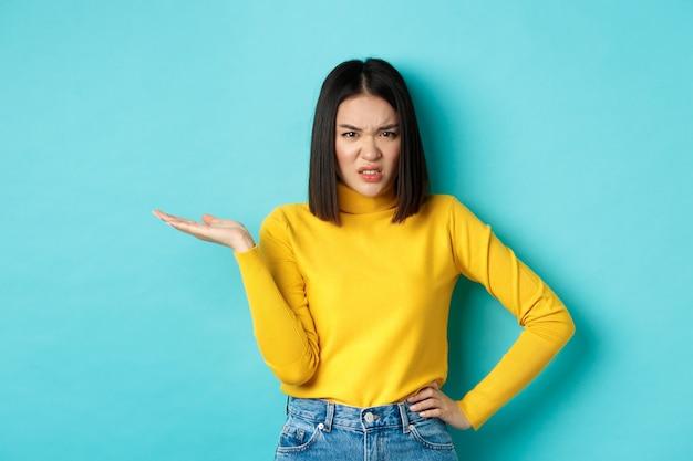 Gefrustreerd en pissig aziatisch meisje dat hand opsteekt en grimassen stoort, starend naar iets met ergernis en teleurstelling, staande over een blauwe achtergrond.