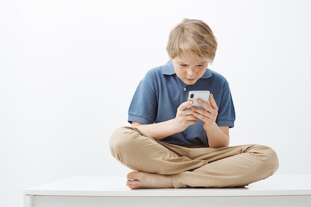 Gefrustreerd intense schattige jonge jongen met blond haar in casual outfit, zittend op gekruiste voeten