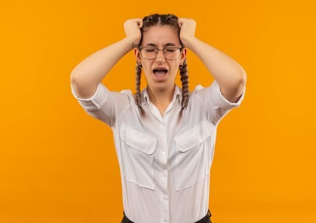 Gefrustreerd jong studentenmeisje in glazen met vlechten in wit overhemd dat wild wordt door haar haar te trekken dat zich over oranje achtergrond bevindt