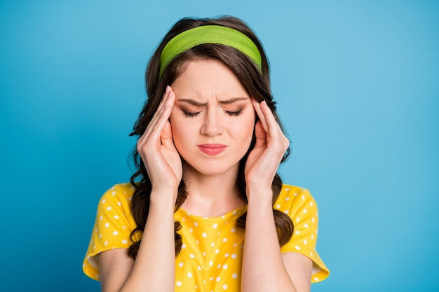 Gefrustreerd meisje lijdt aan pijnlijke migraine aanraking vingers voorhoofd dragen gele groene outfit geïsoleerd op blauwe kleur achtergrond