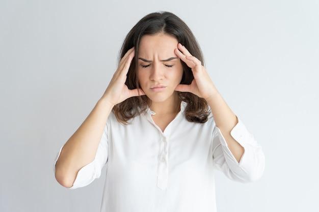 Gefrustreerd moe meisje die aan hoofdpijn lijden.