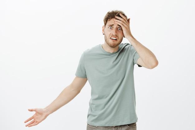 Gefrustreerd nerveus jong mannelijk model in t-shirt, palm aanraken en hand spreiden in clueless gebaar, bezorgd en verward voelen, geen idee hebben hoe hulp en wat te doen