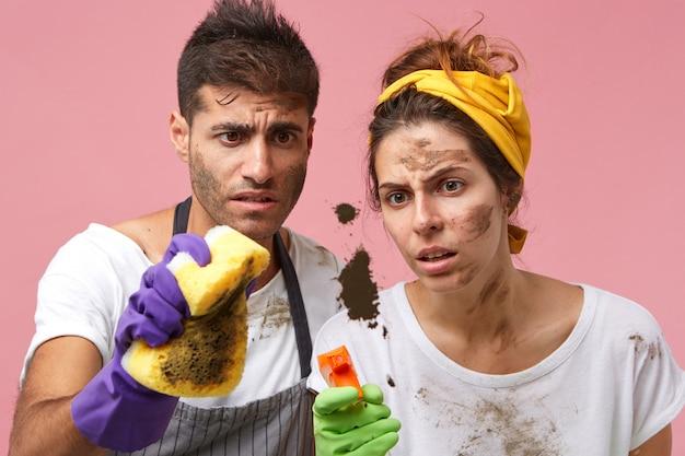 Gefrustreerd vermoeide jonge europese vrouw met hoofdband staan dicht bij haar bebaarde echtgenoot en staren naar vuile plek op vensterglas. huishoudelijk werk en huishoudelijke taken concept