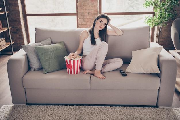 Gefrustreerd verveeld meisje zit divan kijken oninteressante film