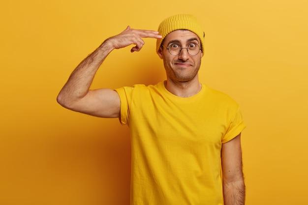 Gefrustreerd volwassen mannetje toont pistoolpistool, houdt vingers bij tempel, fronst gezicht, bedroefd met veel werk te doen, draagt gele hoed en t-shirt