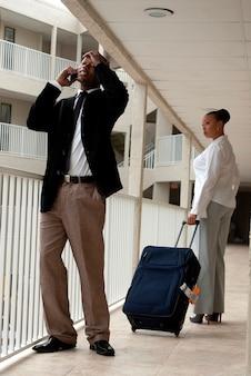 Gefrustreerde afrikaanse mens die op celtelefoon spreekt terwijl op vakantie die zich op hotelbalkon bevindt
