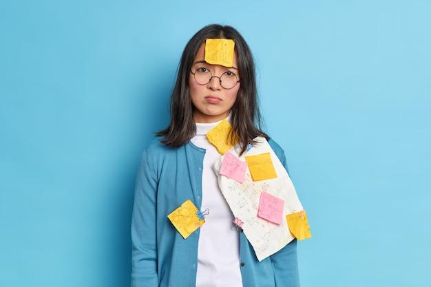 Gefrustreerde aziatische kantoormedewerker heeft veel papierwerk geplakt met herinneringsstickers