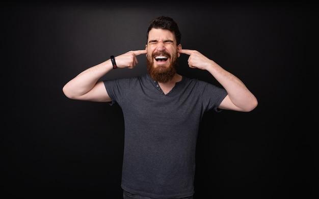 Gefrustreerde bebaarde man die zijn vingers in de oren steekt om het geluid te vertragen, over een donkere geïsoleerde achtergrond