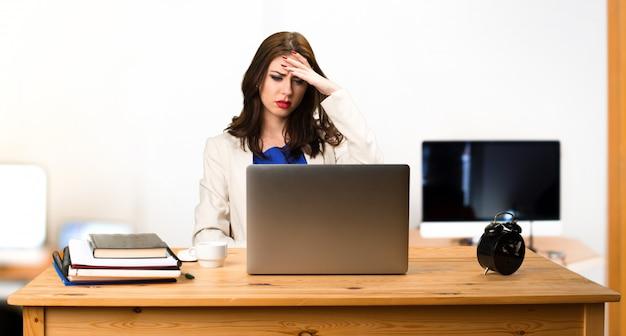 Gefrustreerde bedrijfsvrouw die met haar laptop in het bureau werkt