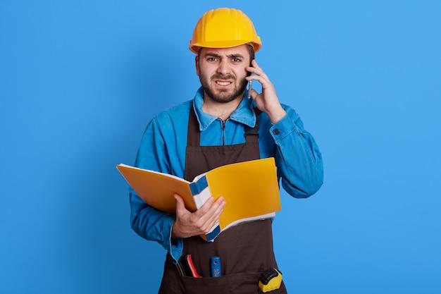 Gefrustreerde bouwvoorman die met werknemer op zijn mobiele telefoon spreekt, boze gezichtsuitdrukking heeft, blauw uniform, gele helm en bruin schort draagt, geïsoleerd op kleurenmuur poseren.