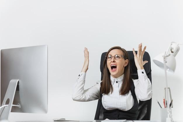 Gefrustreerde boze zakenvrouw zittend aan de balie, werken op de computer met documenten in een licht kantoor, vloeken en schreeuwen, handen omhoog houden, ruimte kopiëren voor reclame