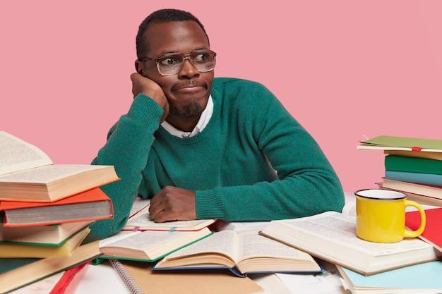 Gefrustreerde donkere jongeman leunt op de hand, drukt op de lippen, draagt een grote bril, denkt na over de beslissing, werkt thuis