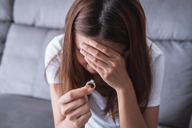Gefrustreerde droevige vrouw die de trouwring opstijgen, jong paar die scheidingsconcept breken