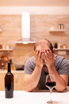 Gefrustreerde dronken jonge man thuis tijdens levenscrisis met een fles rode wijn. ongelukkige persoon ziekte en angst gevoel uitgeput met alcoholisme problemen.