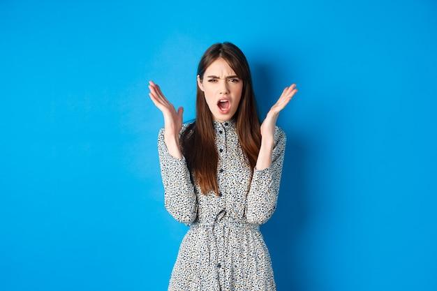Gefrustreerde en boze vrouw in jurk, schreeuwt en fronst naar de camera, steekt woedend handen op, heeft ruzie, staat op blauw.