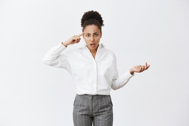 Gefrustreerde en gehinderde afro-amerikaanse zakenvrouw wijzend op het hoofd en scheldt werknemer