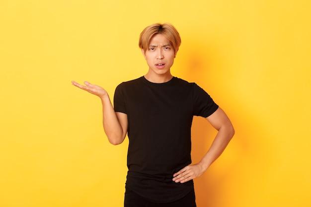 Gefrustreerde en geïrriteerde aziatische man met blond haar, verwarde hand, gele muur opheft