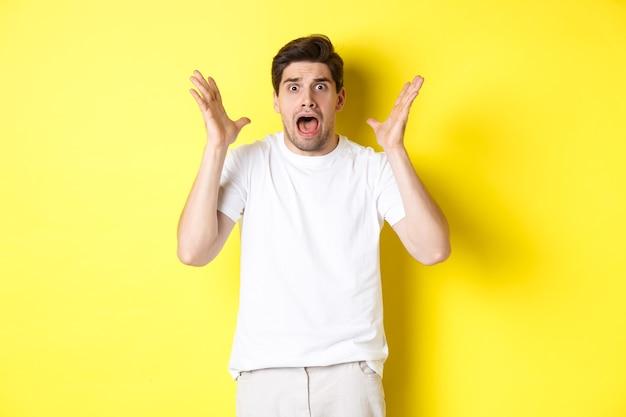 Gefrustreerde en geschokte man die in paniek raakt, schreeuwt en bang kijkt, staande in wit t-shirt op gele achtergrond.