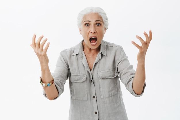 Gefrustreerde en geschokte oude dame die handen schudt en schreeuwt, heeft grote problemen