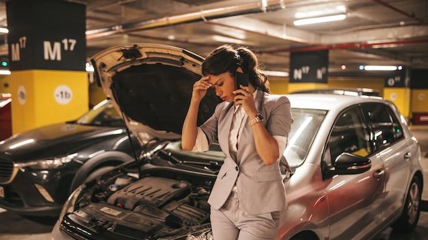 Gefrustreerde en verontruste vrouw heeft een autostoring op een openbare plaats in een ondergrondse garage.