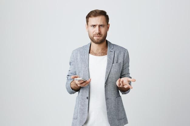 Gefrustreerde fronsende man met smartphone, verward zijn schouders ophalend