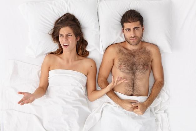Gefrustreerde geïrriteerde vrouw spreidt handen, heeft een slechte relatie met echtgenoot, ligt samen in bed, beweert constant onenigheid te hebben in bed, negeert elkaar. gefrustreerd echtpaar heeft een crisis in de relaties