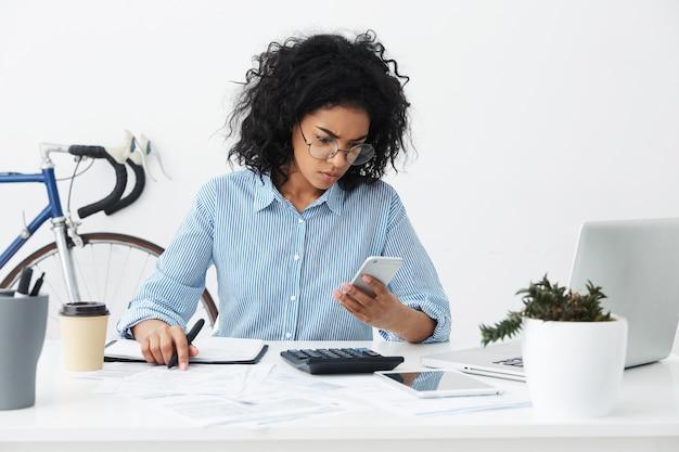 Gefrustreerde jonge gemengde ras vrouwelijke ondernemer die formele overhemd en oogglazen draagt