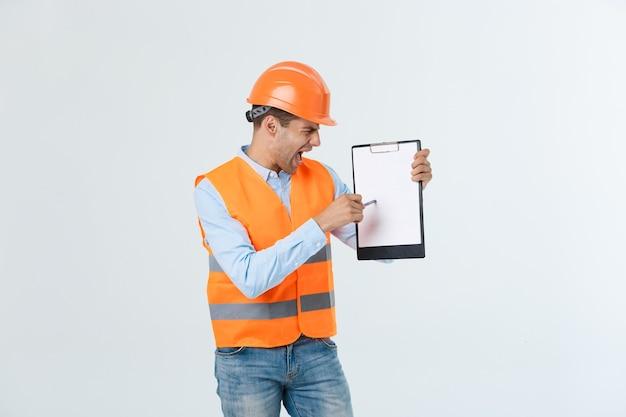 Gefrustreerde jonge ingenieur met veiligheidshelm en reflecterend vest controleren op fout in document over grijze achtergrond.