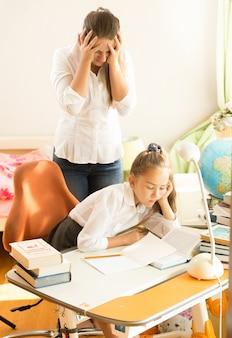 Gefrustreerde jonge moeder die op zoek is naar een dochter die slaapt terwijl ze huiswerk maakt