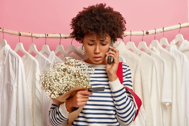 Gefrustreerde jonge vrouw callr via smartphone, kijkt met bezorgde uitdrukking op creditcard, boeket houdt, vormt in de buurt van kledingkast