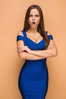 Gefrustreerde jonge vrouw die op bruine muur schreeuwt?
