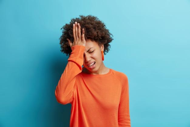 Gefrustreerde jonge vrouw houdt hand op voorhoofd, betreurt verkeerd doen, voelt gestrest gekleed in oranje trui geïsoleerd over blauwe muur