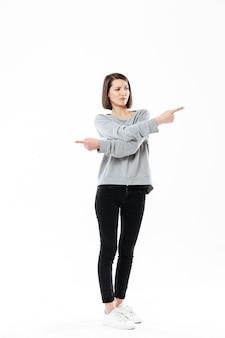 Gefrustreerde jonge vrouw wijzende vingers in beide richtingen