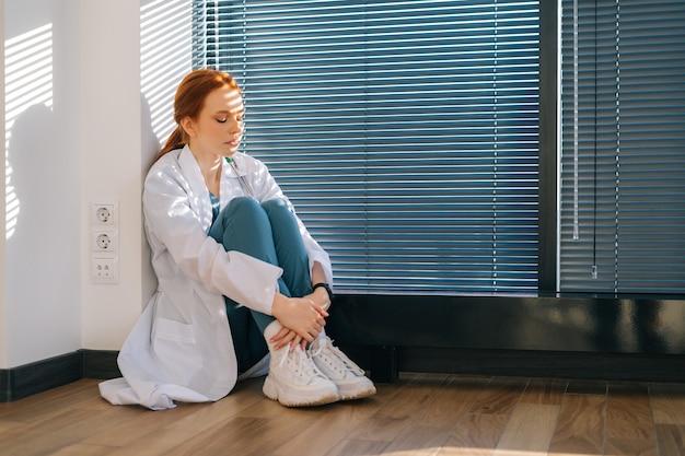 Gefrustreerde jonge vrouwelijke arts in witte jas zittend op de vloer in de buurt van raam met louvre in donkere medische kliniek kantoorruimte en wegkijken. ongelukkige vrouw arts depressie verdrietig voelen