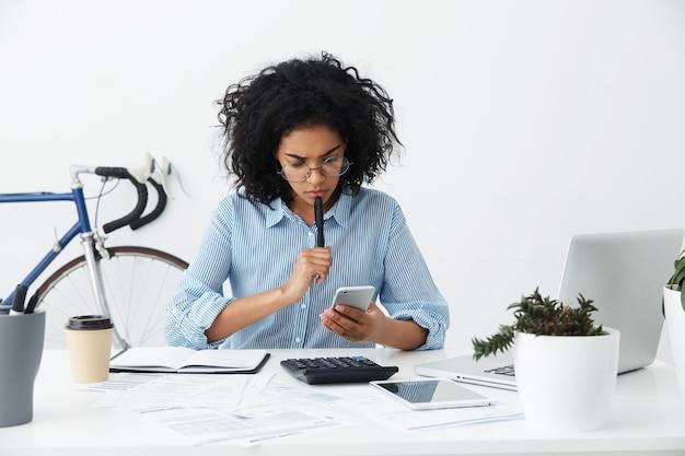 Gefrustreerde jonge vrouwelijke ondernemer in formele overhemd en brillen die een probleem hebben