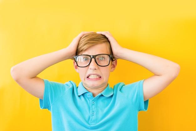 Gefrustreerde jongen die zijn hoofd op een gele achtergrond houdt. studie, moeilijkheden en problemen concept