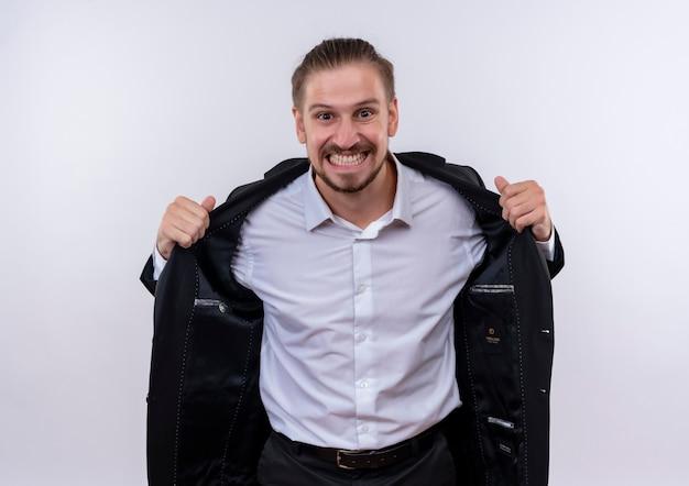 Gefrustreerde knappe zakenman draagt pak kijken camera wild gaan door het opstijgen van zijn pak staande op een witte achtergrond