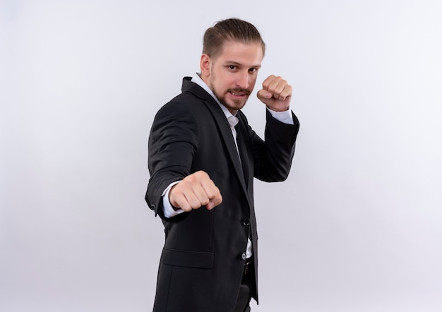 Gefrustreerde knappe zakenman dragen pak gebalde vuisten poseren als bokser staande op witte achtergrond