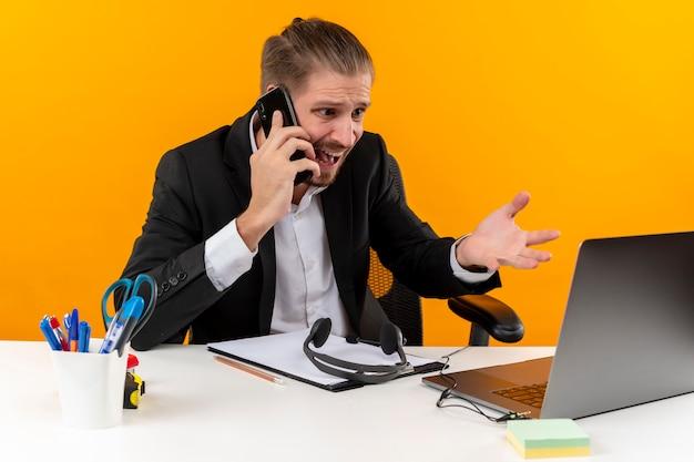 Gefrustreerde knappe zakenman in pak bezig met laptop praten op mobiele telefoon op zoek verward en ontevreden zittend aan de tafel in het kantoor over oranje achtergrond