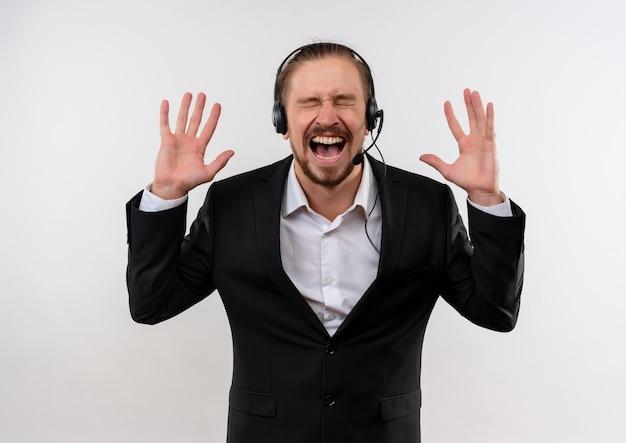 Gefrustreerde knappe zakenman in pak en hoofdtelefoons met een microfoon die en met agressieve uitdrukking schreeuwt die zich over witte achtergrond bevindt