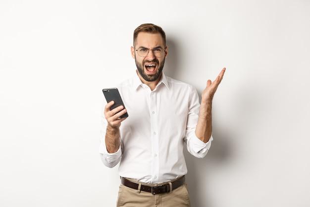 Gefrustreerde man die mobiele telefoon gebruikt en teleurgesteld, klagend, staande kijkt.