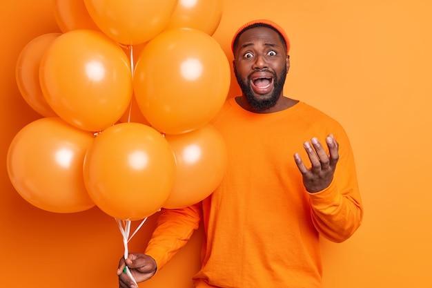 Gefrustreerde man huilt van wanhoop roept luid gebaren houdt actief bos opgeblazen heliumballonnen vast, draagt hoed en casual trui geïsoleerd over oranje muur heeft vakantie