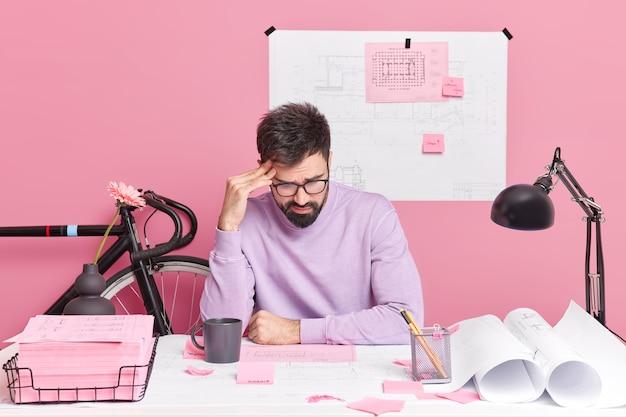 Gefrustreerde mannelijke architect werkt op schets gericht op papieren creats schetsen voor toekomstige bouwproject poses in coworking ruimte gekleed in vrijetijdskleding