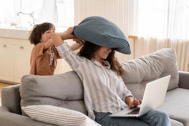 Gefrustreerde moeder probeert thuis te werken, zit met laptop op de bank terwijl zoontje op haar kussen slaat