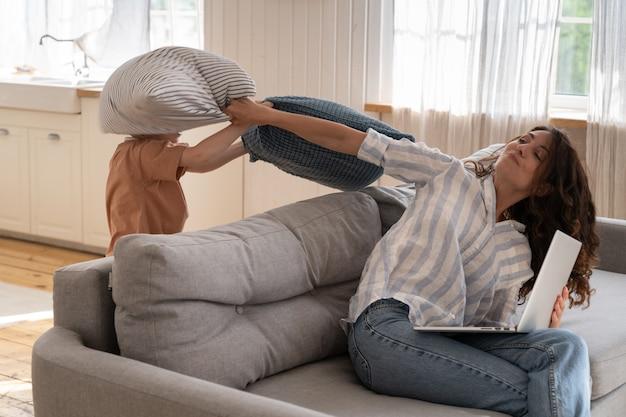 Gefrustreerde moeder slaat speels kind met kussen voor verontrusting van werk, moeder probeert thuis laptop te gebruiken