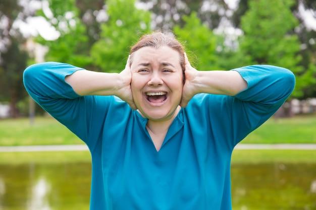 Gefrustreerde ongelukkige vrouw die aan harde geluiden lijdt