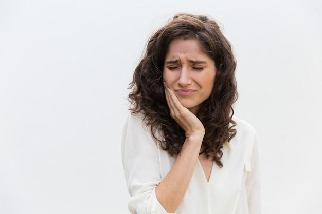 Gefrustreerde ongelukkige vrouw die aan tandpijn lijdt