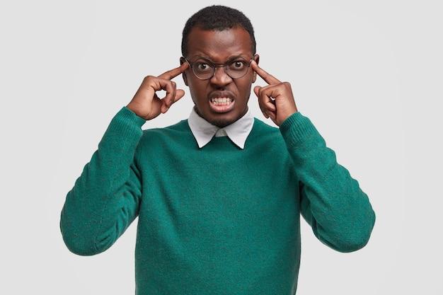 Gefrustreerde ontevreden afro-amerikaanse man houdt beide wijsvingers op de slapen, heeft ontevreden geïrriteerde gezichtsuitdrukking, fronst gezicht met woede